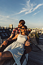 Austria, Vienna, Young couple enjoying romantic sunset on rooftop terrace - AIF000124