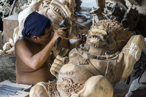 Indonesia, Bali, Ubud, Traditional wood carver's workshop with man working on religious wood sculptures - WE000382
