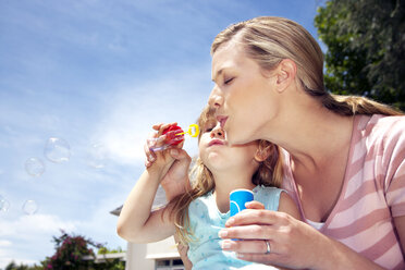 Woman and her little daughter blowing soap bubbles - RMAF000025