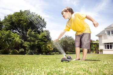 Little boy playing with lawn sprinkler in the garden - RMAF000031