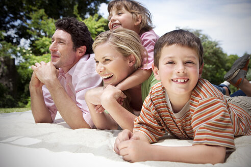 Happy family lying together on blanket in the garden - RMAF000049
