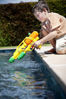 Little boy kneeling with his water gun at pool edge - RMAF000055