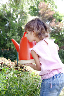Little girl with watering can in the garden - RMAF000058