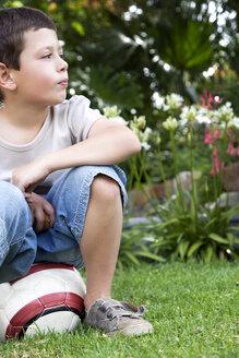 Little boy sitting on soccer ball in the garden - RMAF000067