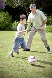 Little boy playing soccer with his grandfather - RMAF000070