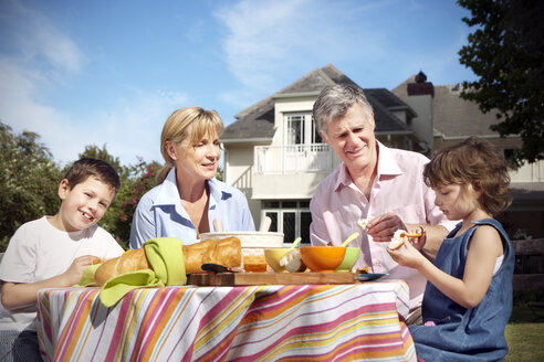 Little boy and girl with their grandparents sitting at dining table in the garden - RMAF000073