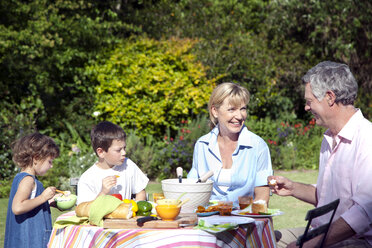 Little boy and girl with their grandparents sitting at dining table in the garden - RMAF000076
