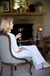Woman with glass of red wine sitting in the living room - RMAF000079