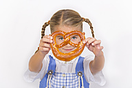Portrait of smiling little girl looking through pretzel - YFF000468
