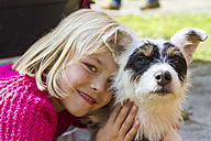 Portrait of smiling litte blond girl and her Jack Russel Terrier - JFEF000730