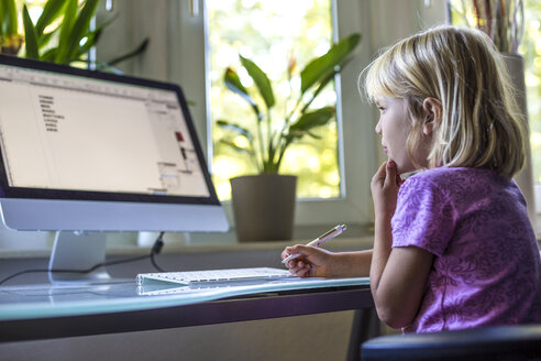 Little girl looking at computer monitor at home - JFEF000733