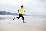 Spain, Ferrol, young man jogging on the beach - RAEF000578