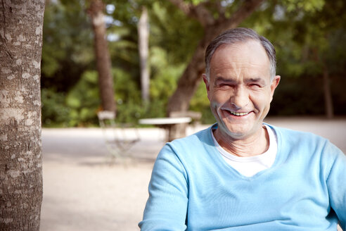 Portrait of smiling mature man sitting in the garden - RMAF000081