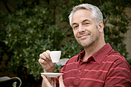 Portrait of smiling man with cup of coffee - RMAF000090