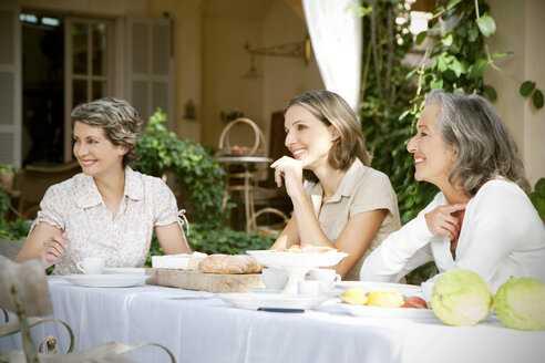 Spain, Mallorca, three female friends sitting at laid table in the garden - RMAF000096