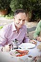 Portrait of smiling man sitting at laid table in the garden communicating with friends - RMAF000099