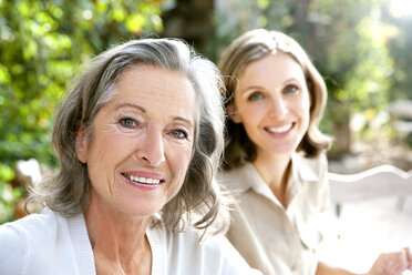 Portrait of smiling mature woman and young woman in the background - RMAF000102