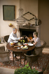 Mature couple sitting at laid table toasting with red wine in front of open fire - RMAF000105