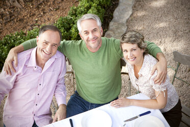 Portrait of three smiling friends sitting in the garden looking up to camera - RMAF000108