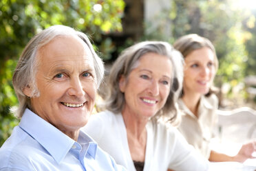 Portrait of smiling senior man and two women in the background sitting  in the garden - RMAF000111