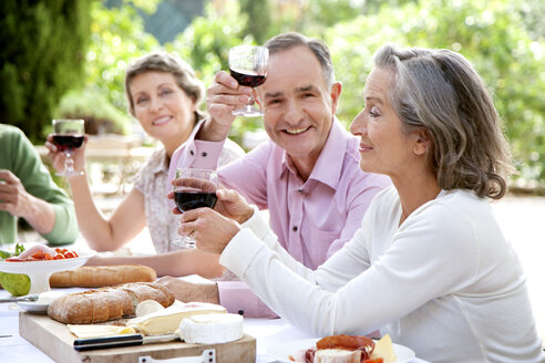 Spain, Mallorca, mature man sitting with friends at laid table in the garden toasting with red wine - RMAF000120