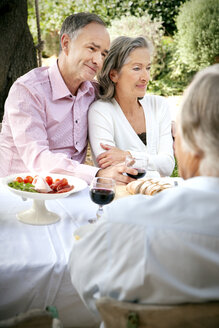 Portrait of mature couple sitting side by side at laid table in the garden - RMAF000123