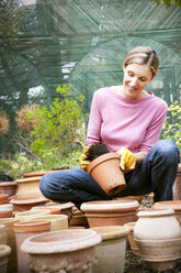 Young woman repotting a plant - RMAF000126