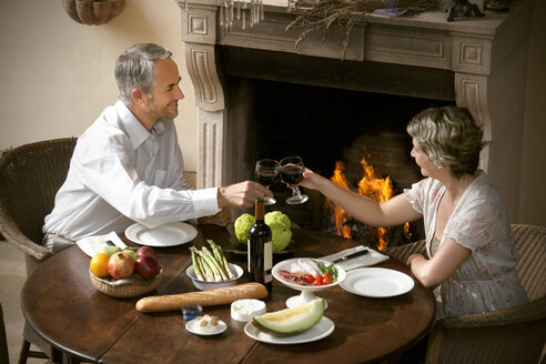 Mature couple sitting at laid table toasting with red wine in front of open fire - RMAF000135