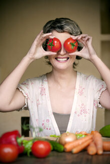 Portrait of smiling woman with tomatoes on her eyes - RMAF000144