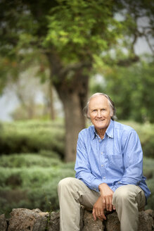 Portrait of relaxed senior senior man sitting on a wall in the garden - RMAF000150