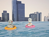 Male and female robot with floating tires swimming in pool in front of city skyline, 3D rendering - UWF000642