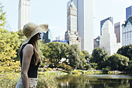 USA, New York City, young woman wearing summer hat in Central Park - GIOF000336