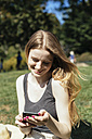 Young woman checking the phone at the park - GIOF000342