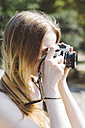 Blond young woman photographing outdoors - GIOF000345