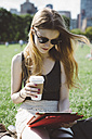 USA, New York City, young woman using digital tablet in Central Park - GIOF000351