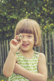 Portrait of smiling little girl holding vineyard snail - LVF004077