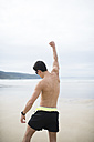 Spain, Galicia, Ferrol, athletic shirtless man on the beach raising his arm - RAEF000591