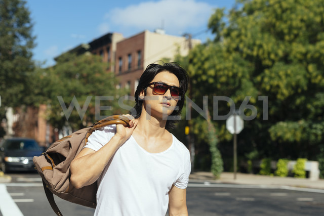 USA, New York City, man carrying a bag walking in Brooklyn - GIOF000371
