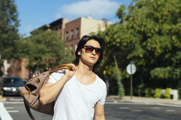 USA, New York City, man carrying a bag walking in Brooklyn - GIOF000371