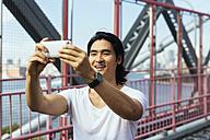 USA, New York City, man on Williamsburg Bridge in Brooklyn taking a selfie - GIOF000377