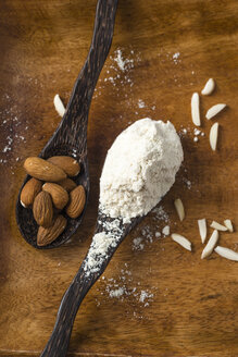 Almond flour and almonds on wooden spoons - MYF001195