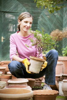 Smiling woman looking at potted plant in garden - RMAF000158