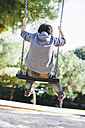 Rear view of boy on a swing at the playground - EBSF000997