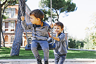 Boy pushing brother on a swing at the playground - EBSF001003
