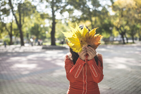 Woman covering her face with autumn leaves - DEGF000571