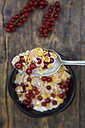 Bowl of yogurt with cornflakes and red currants, spoon - LVF004088