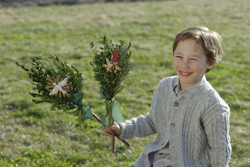 Germany, Upper Bavaria, Portrait of smiling little boy with Palmbusch on a meadow - LBF001270