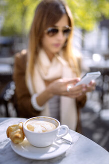 Spain, Gijon, Cup of cappucino, young woman in background using smart phone - MGOF000969