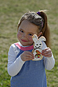 Portrait of smiling little girl showing pastry formed like an Eastern Bunny - LBF001273
