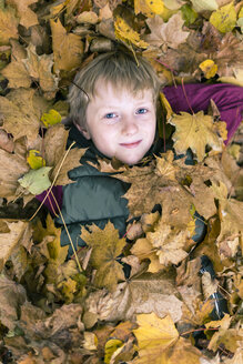 Portrait of boy lying on the ground covered with autumn leaves - SARF002260